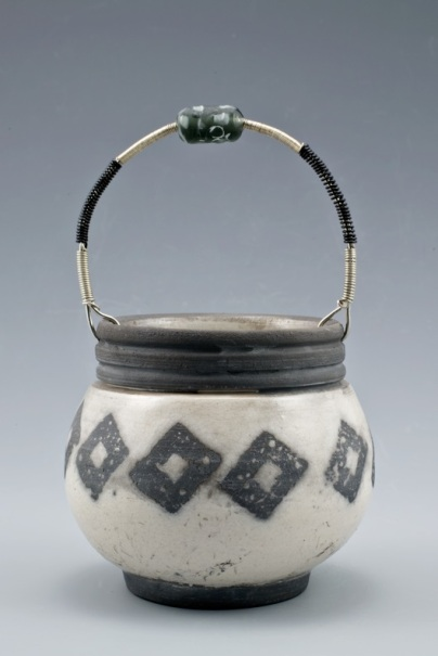 Smith, Image #1, Black & White Raku Basket, 6_ H x 5_W x 5_L, B-Mix Stoneware, Clear Crackle Raku Glaze with waxed shapes, Wrapped wire Handle w Handmade Glass Bead, Raku
